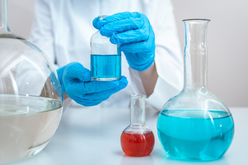 Chemist woman holding medical glass bottle with liquid, making laboratory research