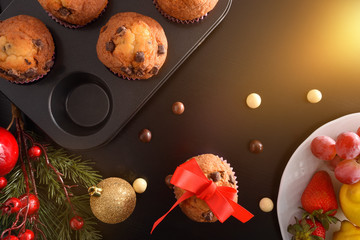 Homemade baked chocolate muffins on black christmas table top flash