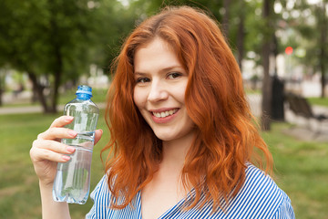 pure drinking water, young red-haired girl with a bottle of water, bottled water