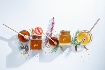 In de dag Bee Composition of honey jars with honey sticks ,flowers and bee pollen on white background