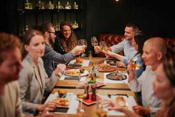 Group of best friends sitting in restaurant, having dinner, drinking wine and having fun. Wall mural