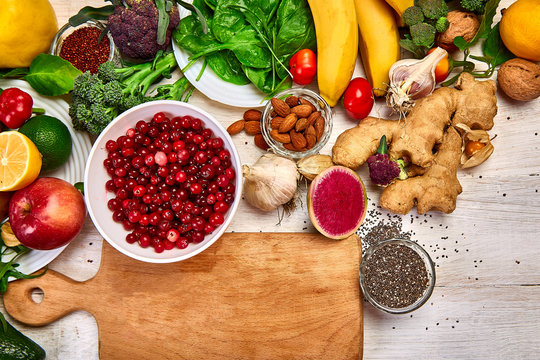 Selection food of rich in antioxidants and vitamins and mineral sources, on white wooden background around cutting board. Healthy balanced dieting concept, ingredients for cooking. Top view, flat lay