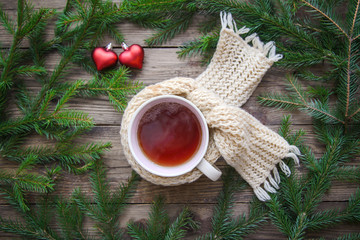 Cozy picture with a mug of tea in a scarf, Christmas tree branches and hearts on a wooden background