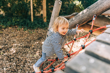 Outdoor portrait of happy toddler girl playing on playground, active child having fun in kids park
