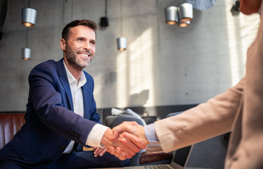 Business people shaking hands during meeting in cafe