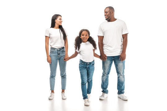 happy african american husband and wife looking at each other while holding hands with adorable daughter on white background
