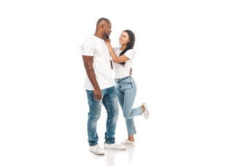 cheerful african american woman touching face of handsome husband on white background