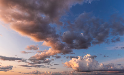 Amazing beautiful sunny sunset or sunrise white clouds running along peaceful clear blue sky in evening or morning. Great natural background. Horizontal color photography.