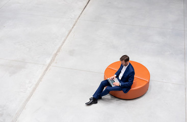 Fototapeta Businessman using laptop sitting alone top view, copy space background
