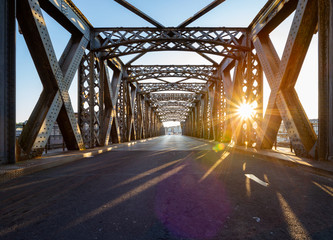 Asphalt road under the steel construction of a bridge in the city on a sunny day. Evening urban...