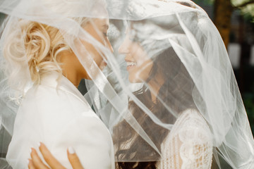 Foreground of a lesbian brides nearly kissing through the wedding veil