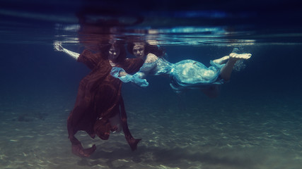 Two girls in dresses play underwater