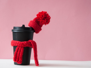 Beautiful cozy Christmas picture with a mug of hot coffee in a scarf and hat over pink background