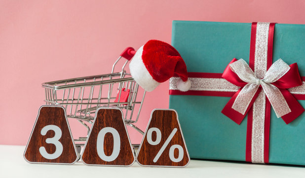 Christmas sale. Big sale 30%, thirty percent with Santa hat and christmas gift box over pink background.