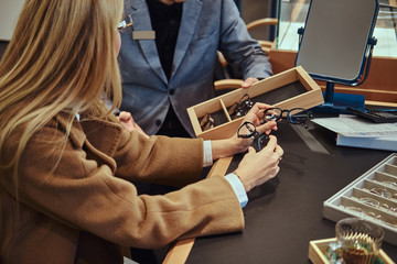 Blonde woman is choosing new pair of glasses while shop assistant is showing her variety of glasses.