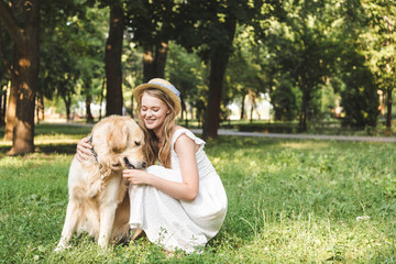 Wall Mural - beautiful girl in white dress and straw hat petting golden retriever while sitting on meadow