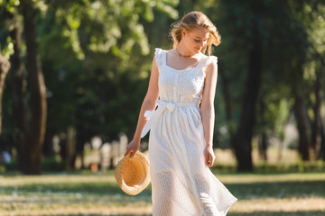 Wall Mural - beautiful girl in white dress holding straw hat while smiling and standing on meadow and looking down
