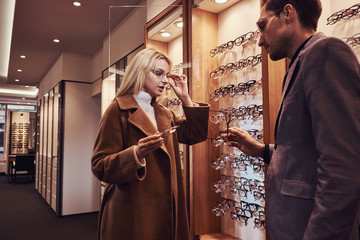 Professional male consultant is helping to choose new glasses to female customer at optic shop.
