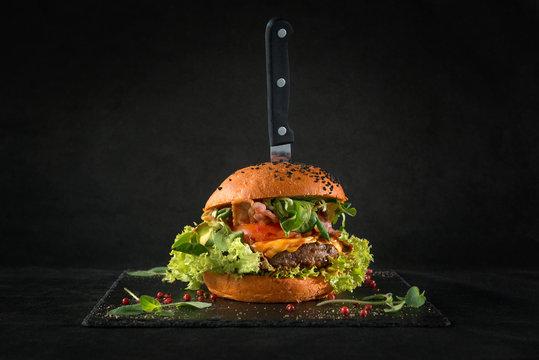 Beef burger on black background. For fast food restaurant design or fast food menu