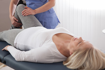 Therapist treating injured knee of famale patient in hospital - physical therapy concept