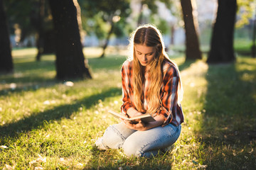 Wall Mural - full length view of beautiful girl in casual clothes sitting on meadow in sunlight and reading book