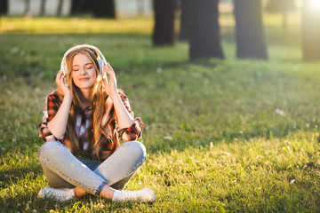 Wall Mural - full length view of beautiful girl in casual clothes sitting with crossed legs on meadow in sunlight and listening to music on headphones