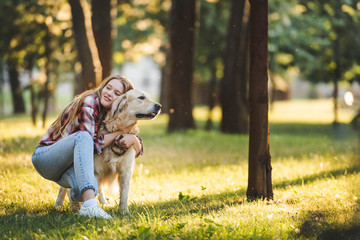 Wall Mural - full length view of beautiful young girl in casual clothes hugging golden retriever while sitting on meadow in sunlight and looking away