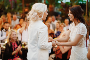 Two beautiful lesbian brides lust married are laughting and holding hands in front of guests
