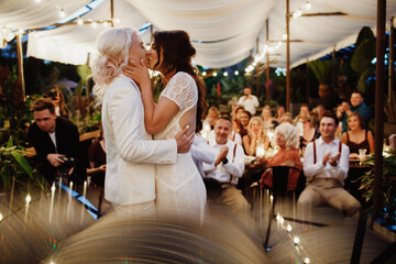 Lesbian couple is kissing in front of guests on the wedding ceremony at the terrace in the evening