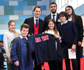 John Elkann poses with children which gave him the sweatshirt with the logo of the city during a ceremony to inaugurate a school dedicated to former Fiat CEO Sergio Marchionne in Amatrice