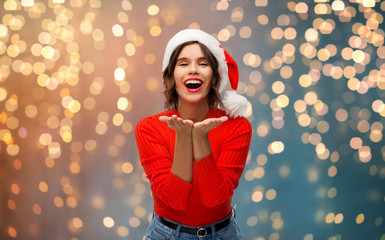 christmas, holidays and people concept - happy smiling young woman in santa helper hat sending air kiss over grey background