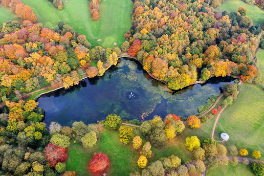 Aerial photo in autumn showing the beautiful autumn fall colours of a park in Leeds known as Roundhay Park in West Yorkshire UK, showing a typical British park and woods along side a lake.