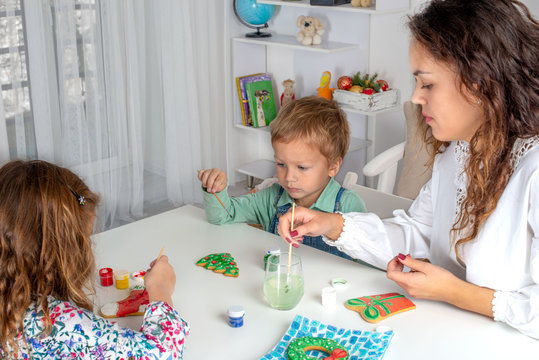 Little children with a nanny  to prepare for Christmas.  They sit at the table in the room