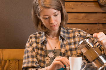 A blonde girl in a plaid shirt at a table in a cafe and drinks tea or coffee.