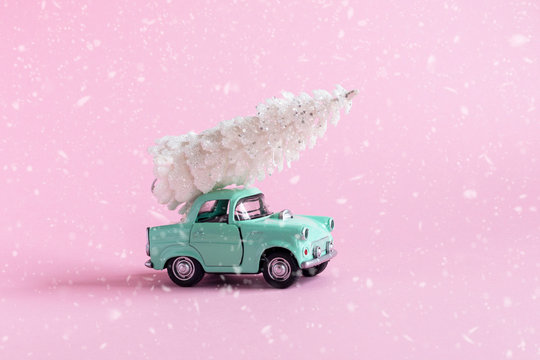 toy car with Christmas tree on it on pink background with snow texture , Christmas pr