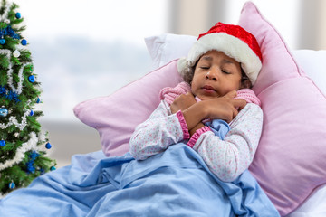 little girl wearing Santa hat seem to be cold while she is in bed at hospital or at home