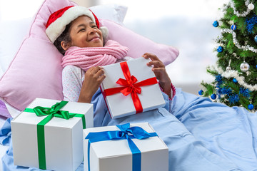 little girl wearing Santa hat receiving her gift while she is in hospital or at home
