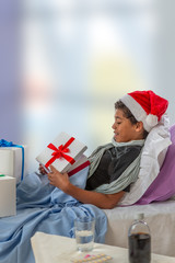 little boy wearing Santa hat receiving her gift while she is in hospital or at home