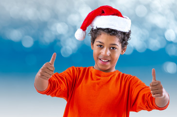 Teen boy in a Santa Claus hat shows two thumbs over blue bokeh background