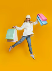 Girl in winter clothes with colorful shopping bags jumping up