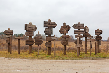 Wooden pointers in the form of an arrow on wooden columns in the field, place for your text