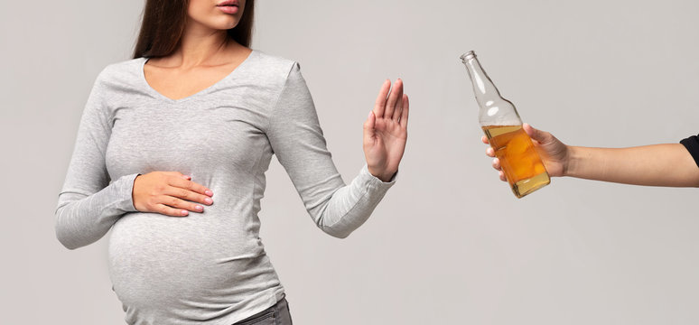 Unrecognizable Pregnant Girl Gesturing Stop To Beer Bottle, Gray Background