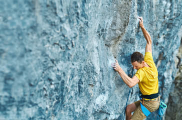 top view young strong man rock climber climbing on a high vertical limestone cliff, reaching holds, making hard wide move and gripping hold, attaching rope. Conquering, overcoming and active lifestyle