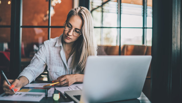 Young focused woman working with chart