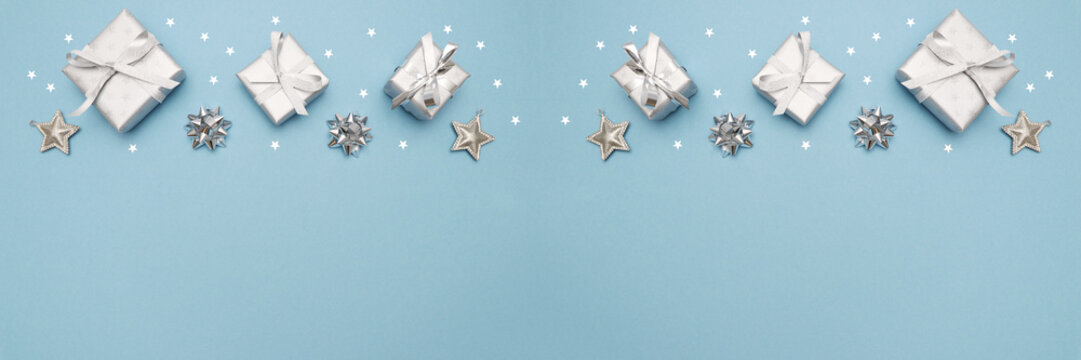 Gifts or present boxes in silver with silver bows and tree ball ornaments and little silver stars, table tob view. Composition for Christmas. Blue pastel background.