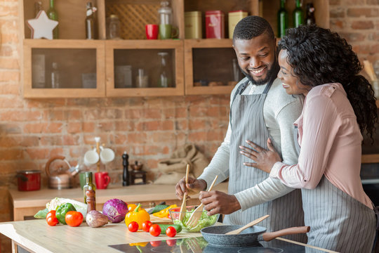 Thankful african lady hugging her husband, cooking together