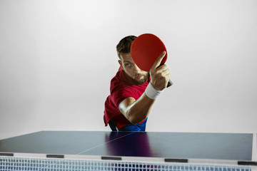 Wall Mural - Possibility. Young man plays table tennis on white studio background. Model plays ping pong. Concept of leisure activity, sport, human emotions in gameplay, healthy lifestyle, motion, action, movement