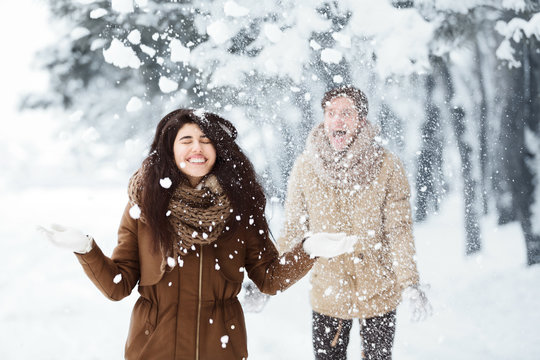 Couple Throwing Snow Having Fun In Winter Forest