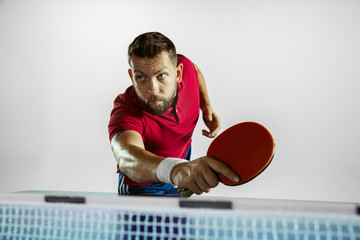 Wall Mural - Speed. Young man plays table tennis on white studio background. Model plays ping pong. Concept of leisure activity, sport, human emotions in gameplay, healthy lifestyle, motion, action, movement.