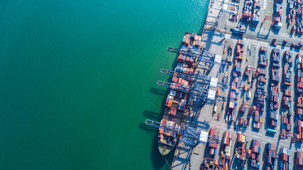 Container ship at industrial port in import export business logistic and transportation of international by container ship in the open sea.